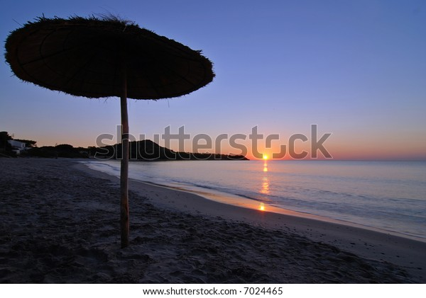 Umbrella silhouette on the beach during the sunrise