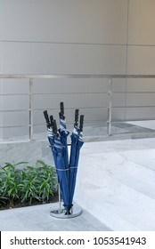 Umbrella Stand : Many blue folded umbrellas in glass plastic container box stored. Prepare for guest to outdoor in raining day.