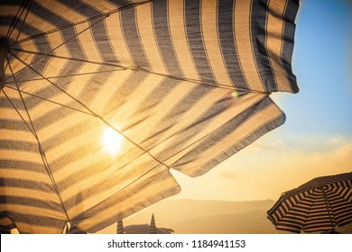 Umbrella and sun in front at sunset on sandy city beach on sea shore ocean Concept of tourism travel and body skin protection from melanoma skin cancer sunburn.