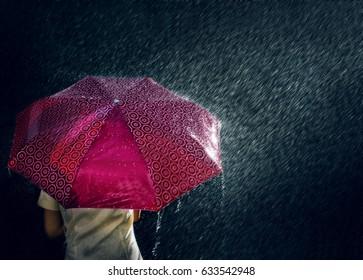 Umbrella under raindrops in dark night