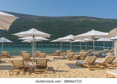 Sonnenschirme und Strandliegen am goldenen Strand, Montenegro