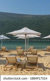Sonnenschirme und Strandliegen am goldenen Strand mit blauem Himmel, Montenegro