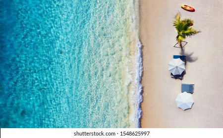 Umbrellas, Beach and ocean as a background from top view. Azure water background from top view. Summer seascape from air. Travel - image