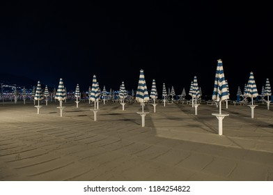 umbrellas closed on the beach at night
