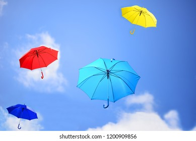Umbrellas colorful variety over bright blue sky background.