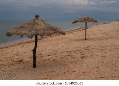 umbrellas made of bamboo and reeds stand on the beach near the ocean. the rainy season, the clouds in the sky, the deserted wild beach