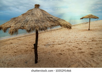 umbrellas made of bamboo and reeds stand on the beach near the ocean. sunrise or sunset, a great time to travel and rest
