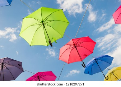 Umbrellas in many colors in Vejle, Denmark. Colorful umbrellas background. Hanging umbrellas over blue sky.