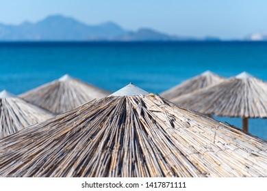Umbrellas on Kardamena city beach in Kos island, Greece.