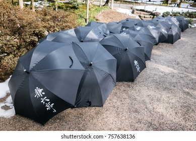 Umbrellas in a Row, Kenroku-en, Kanazawa, Japan. Characters on Umbrella Translate to 'Kenroku-en' or 'Kenroku Garden'.