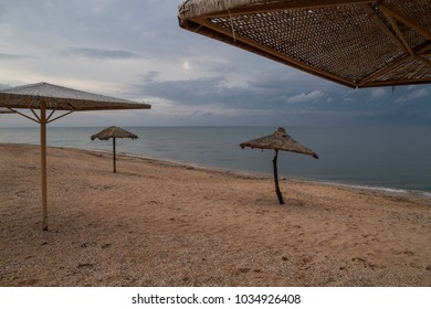 umbrellas stand along the beach near the water. Travel and tourism on the shore of ocean and sea.