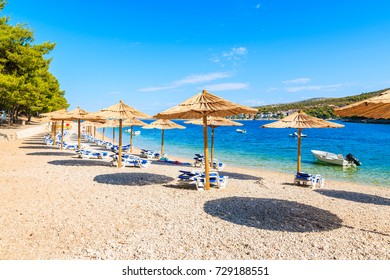 Umbrellas with sunbeds on beach in Primosten town, Dalmatia, Croatia