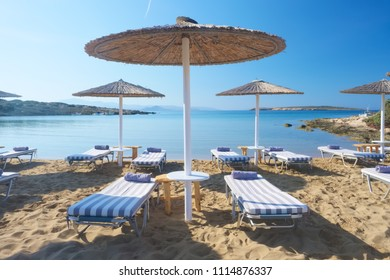 Umbrellas with sunbeds on beautiful sandy Santa Maria beach with turquoise sea water, Paros island, Greece