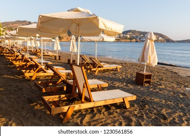 umbrellas and sunbeds on a beautiful sandy beach by the sea in the sunset and sunrise