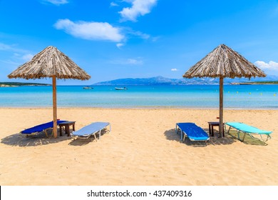 Umbrellas with sunbeds on beautiful sandy Santa Maria beach with turquoise sea water, Paros island, Greece