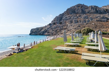 Umbrellas and sunbeds on green grass on Kolymbia beach (Rhodes, Greece)
