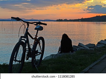 Umbria, Italy, landscape of Trasimeno lake at sunset. A girl has left her bicycle and enjoys the scenery