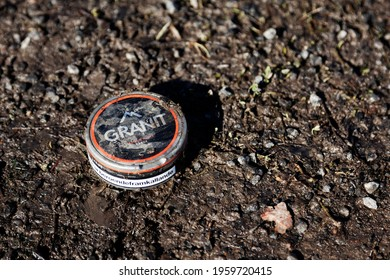 Umea, Norrland Sweden - April 7, 2021: a snuff box is in mud and dirt. text: - Granite, addictive tobacco
