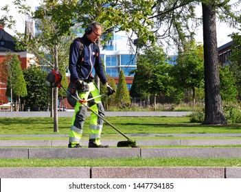 Umea, Sweden - August 21, 2018: a man working on cutting the grass in Umea city