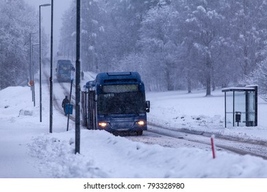 UMEA, SWEDEN ON DECEMBER 11. View of buses, a bus stop along a snowy road on December 11, 2017 in Umea, Sweden. Hill and trees in the background.