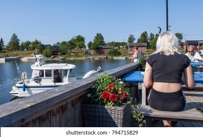 UMEA, SWEDEN ON JULY 27. View of a bridge, balcony close to the sea on July 27, 2017 in Rovagen, Sweden. Unidentified guests by the tables, marina to the left.