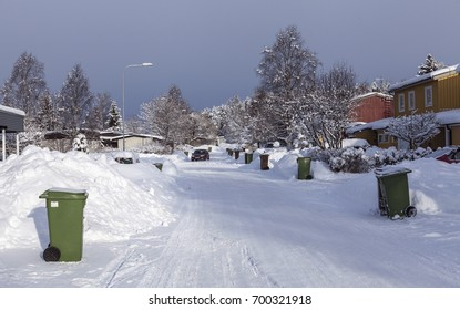 UMEA, SWEDEN ON MARCH 03. View of a street in snow with recycling containers, dust-bins next to the houses on March 03, 2017 in Umea, Sweden. Car in the background.