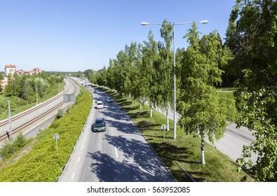 UMEA, SWEDEN ON MAY 29. View of the highway and newly built railway in urban, residential area on May 29, 2013 in Umea, Sweden. Trees and buildings.