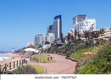 UMHLANGA, DURBAN, SOUTH AFRICA - OCTOBER 31, 2017: Many unknown visitors and promenade on beachfront against coastal commercial and residential city skyline in Umhlanga, Durban South Africa