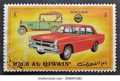 Umm al - Qaiwain - circa 1972 : Cancelled postage stamp printed by  Umm al-Qaiwain, that shows Old and new version of Nissan vehicle, circa 1972.