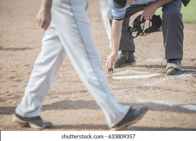 Umpire cleans home plate as next batter comes up to bat