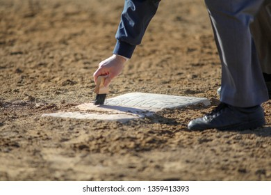 umpire clearing dirt from base