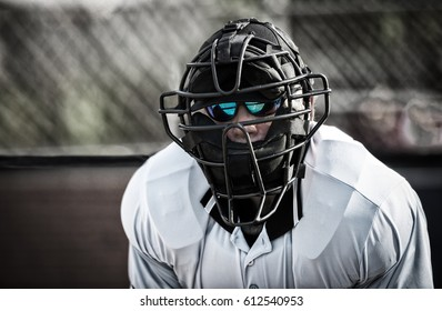 Umpire in colorful sunglasses and face mask, behind home plate, looking at camera