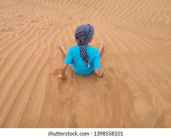 un enfant qui contemple le silence dans le désert de Dubaï