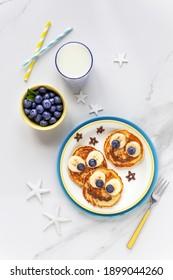 Auf den süßen Pfannkuchen zum Frühstück mit Bananen, frischen Blaubeeren und Brombeeren. Kreative Küche für Kinder