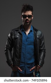 un shaved sexy man in leather jacket and sunglasses standing with hands in pockets