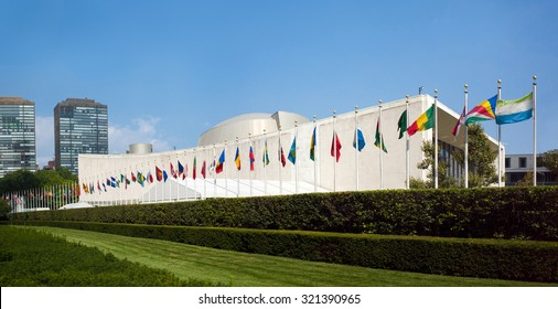 UN United Nations general assembly building with world flags flying in front - First Avenue, New York City, NY, USA