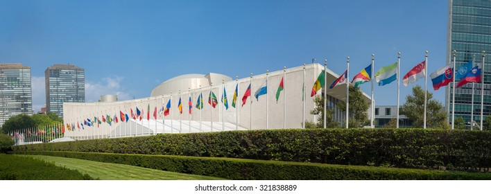 UN United Nations general assembly building with world flags flying in front - September 1, 2015, First avenue, New York City, NY, USA