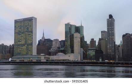 UN United Nations secretariat and General Assembly building with light in windows viewed across East River before sunset - January 11, 2017, 1st Avenue, New York City, NY, USA