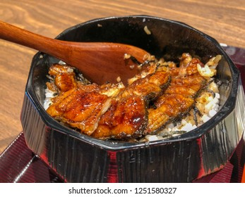 Unagi donburi's a bowl filled with steamed white rice,topped with fillets of eel (unagi),glazed with a sweetened soy based sauce, called tare and caramelized. Wooden spoon left in, look take some.