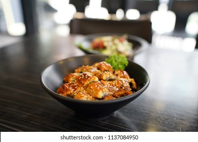 Unagi Donburi -  A bowl of steamed rice topped with grilled eel and white sesame on wooden table, Traditional Japanese Food.