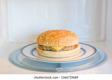 Unappealing microwavable cheese burger on a plate in a microwave oven a bad diet concept