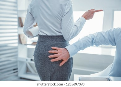 Unappropriated gesture. Shameless man touching back of woman who wearing office skirt at office
