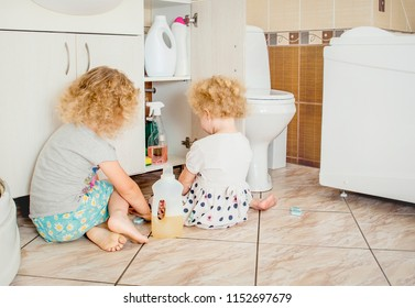 Unattended children play quietly at bathroom with dangerous household chemicals. Safety hazard at home concept. Keep away from children`s reach.