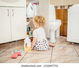 Unattended girl child play quietly at bathroom with dangerous household chemicals. Safety hazard at home concept. Keep away from children`s reach.