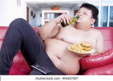 Unattractive overweight man sitting on the red sofa while drinking beer and eating junk food in front of tv at living room