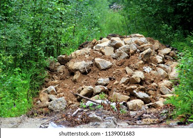 Unauthorized garbage dump in wild (forest, park): pieces of asphalt, metal fittings, brown clay; background of green plants. Concept: ecology; environmental pollution – destructive role of man
