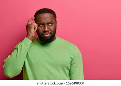 Unaware confused black man scratches head, frowns while looks aside, feels doubt or hesitation while making decision, wears green jumper, isolated on pink studio wall, finds solution, solves puzzle