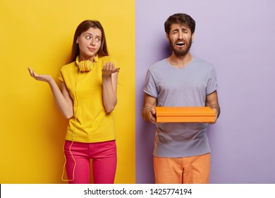 Unaware questioned girl spreads palms with hesitation, has no idea what is in box, frustrated man has sorrowful dejected expression, carries package wants to present it to girlfriend poses indoor
