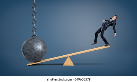 An unbalanced businessman standing on a wooden seesaw and overweighed by a wrecking ball. Unfair disadvantage. Weight of problems. Unresolved complications.
