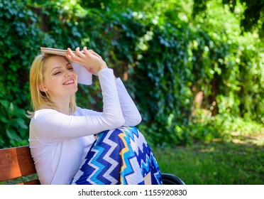 Unbelievable ending. Girl sit bench relaxing with book, green nature background. Lady pretty bookworm dreamy read book outdoors sunny day. Woman dreamy smiling reading book in garden.